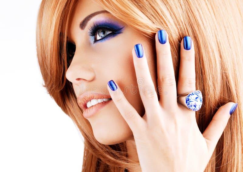 Retrato de uma mulher bonita com pregos azuis, composição azul fotografia de stock