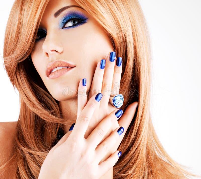 Retrato de uma mulher bonita com pregos azuis, composição azul foto de stock