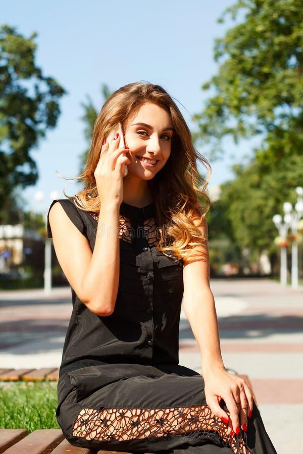 Retrato de uma mulher bonita de sorriso dos jovens que fala no telefone foto de stock