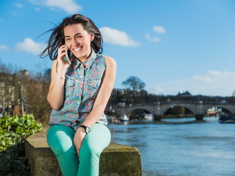 Retrato de uma mulher bonita de sorriso que fala no telefone imagens de stock royalty free