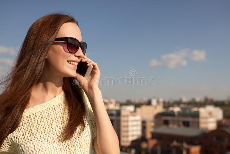 Retrato de uma mulher bonita de sorriso que fala no telefone fotografia de stock