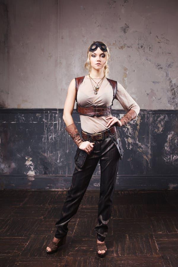 Retrato de uma mulher bonita do steampunk em vidros do aviador sobre o fundo cinzento imagem de stock royalty free