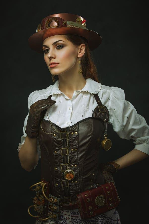 Retrato de uma mulher bonita do steampunk sobre o fundo escuro fotografia de stock