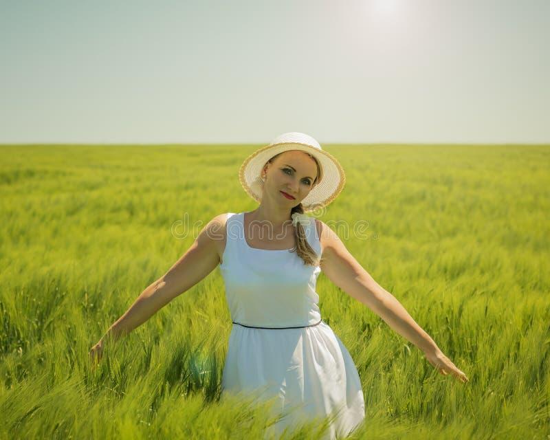 Retrato de uma mulher bonita em um dia de verão quente em um campo do centeio verde foto de stock