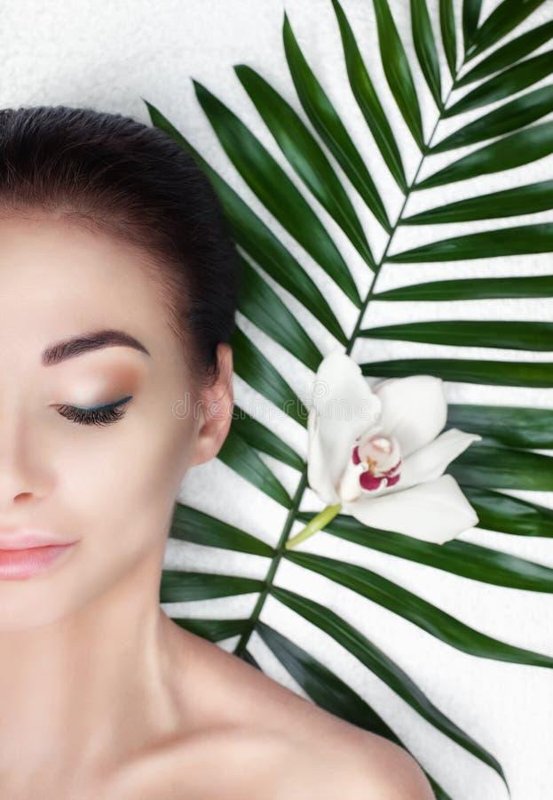 Retrato de uma mulher bonita em um salão de beleza dos termas na frente de um tratamento da beleza fotografia de stock