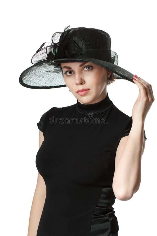 Retrato de uma mulher bonita em um vestido e em um chapéu pretos isolados imagens de stock royalty free