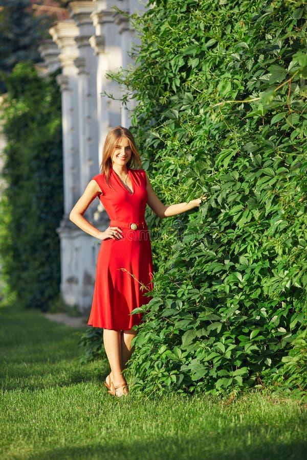 Retrato de uma mulher bonita em um vestido vermelho no parque imagem de stock royalty free