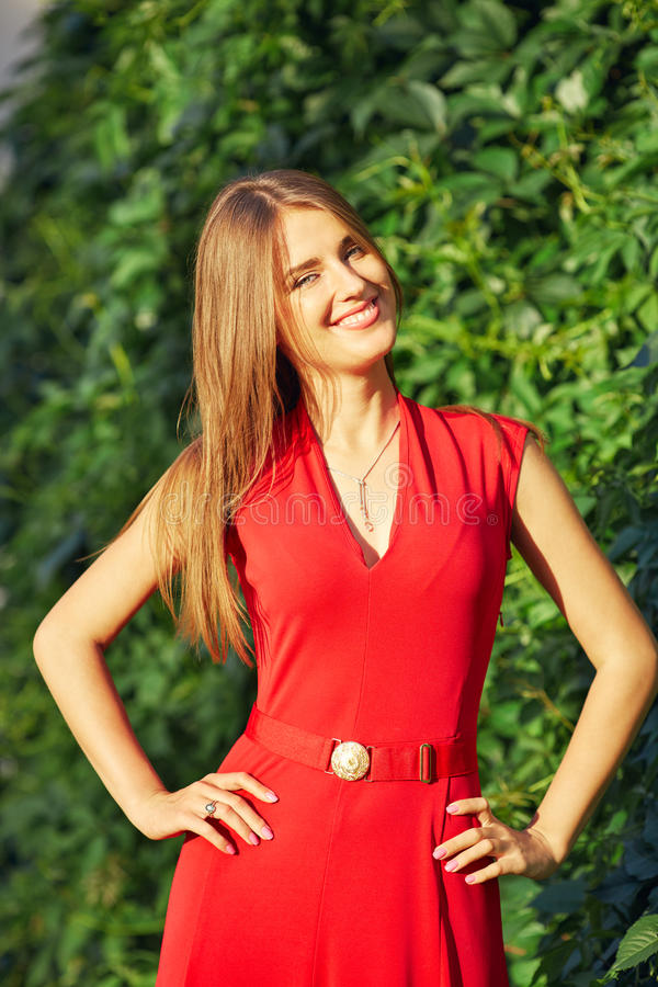 Retrato de uma mulher bonita em um vestido vermelho no parque fotografia de stock royalty free