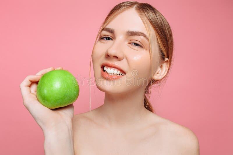 Retrato de uma mulher bonita feliz que guarda uma maçã, em um fundo cor-de-rosa fotografia de stock royalty free