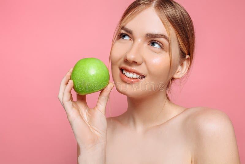 Retrato de uma mulher bonita feliz que guarda uma maçã, em um fundo cor-de-rosa fotografia de stock