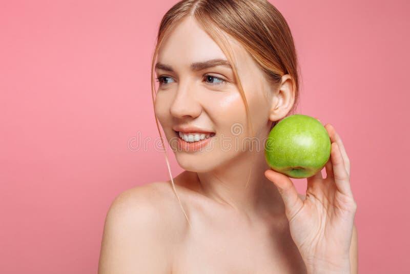 Retrato de uma mulher bonita feliz que guarda uma maçã, em um fundo cor-de-rosa imagem de stock royalty free