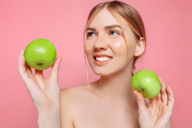 Retrato de uma mulher bonita feliz que guarda uma maçã, em um fundo cor-de-rosa foto de stock