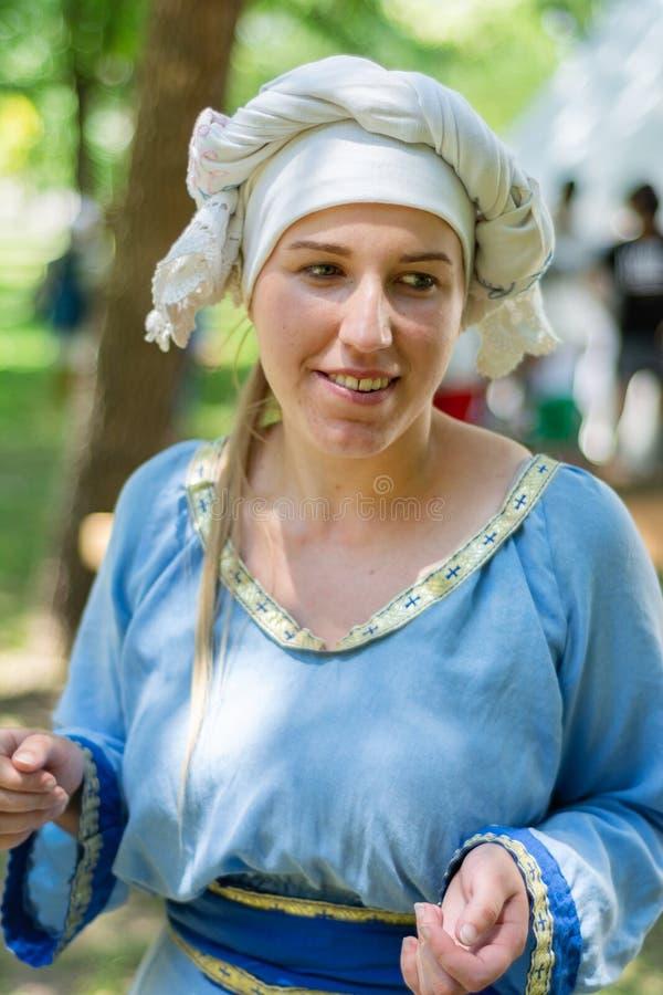 Retrato de uma mulher bonita medieval em um vestido tradicional azul e em um tampão branco imagens de stock