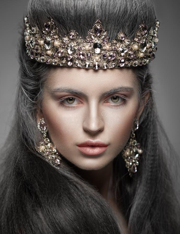 Retrato de uma mulher bonita na coroa e nos brincos do diamante imagem de stock royalty free