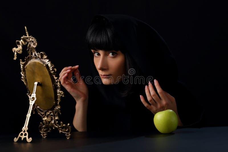 Retrato de uma mulher bonita na frente de um espelho de bronze velho fotos de stock