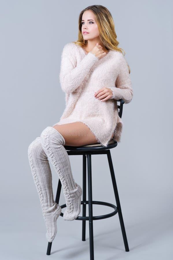 Retrato de uma mulher bonita na roupa feita malha trandy imagem de stock