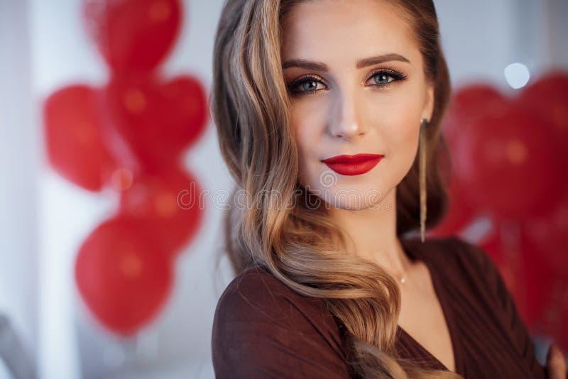 Retrato de uma mulher bonita no dia do ` s do Valentim em um fundo de balões de ar vermelhos fotos de stock