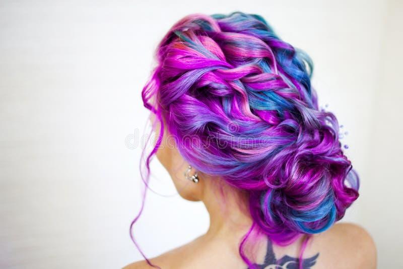 Retrato de uma mulher bonita nova com cabelo colorido M?scaras brilhantes de azul e de roxo, cabelo do inclina??o imagens de stock royalty free