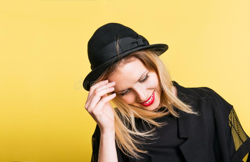 Retrato de uma mulher bonita nova com o chapéu negro no estúdio em um fundo amarelo fotografia de stock