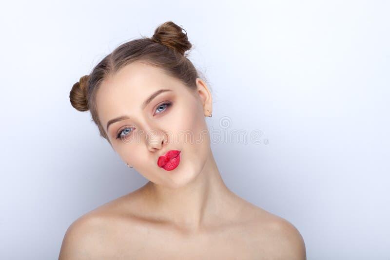 Retrato de uma mulher bonita nova com penteado engraçado do bolo dos bordos vermelhos brilhantes na moda da composição e ato dese foto de stock
