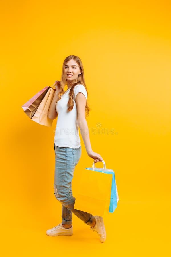 Retrato de uma mulher bonita nova em um t-shirt branco, com sacos multi-coloridos, em um fundo amarelo fotos de stock