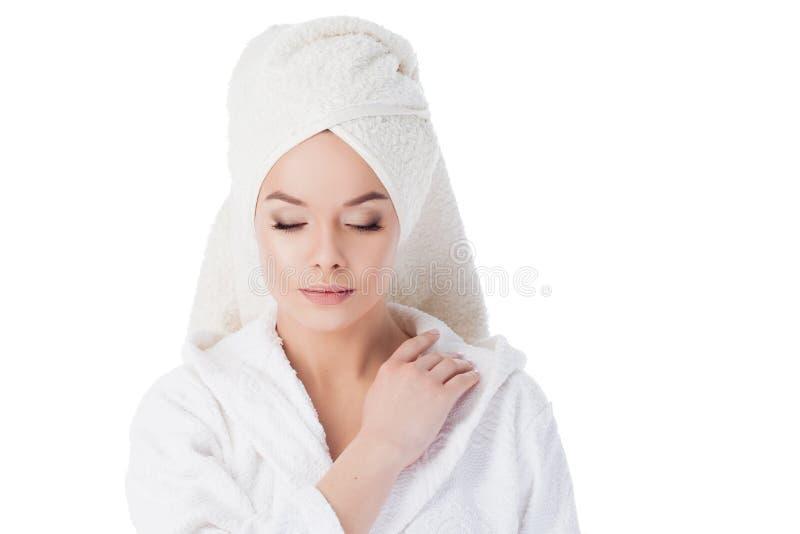 Retrato de uma mulher bonita nova em uma veste de Terry e com uma toalha em sua cabeça Beleza e cuidados com a pele fotografia de stock royalty free