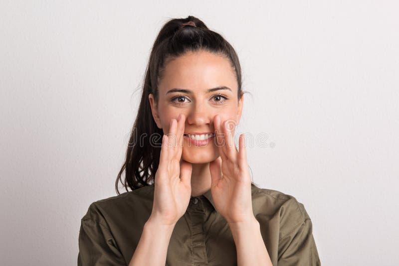 Retrato de uma mulher bonita nova no estúdio, mãos colocadas em torno de sua boca fotos de stock royalty free