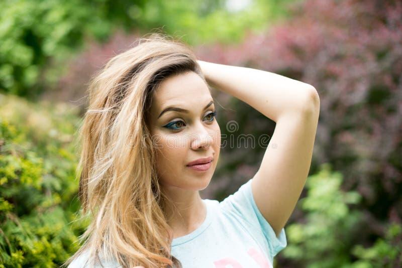 Retrato de uma mulher bonita nova nos vidros, em uma natureza verde do verão do fundo imagens de stock