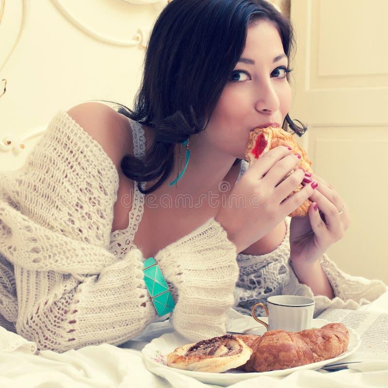 Retrato de uma mulher bonita nova que come seu croissant foto de stock royalty free