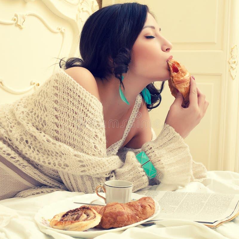 Retrato de uma mulher bonita nova que come seu croissant com st imagem de stock