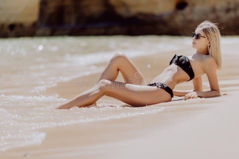 Retrato de uma mulher bonita nova que encontra-se na areia na praia do oceano fotos de stock royalty free