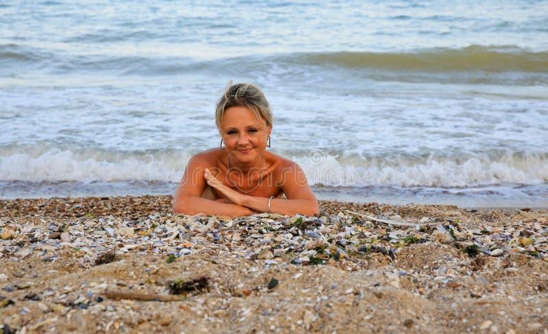 Retrato de uma mulher bonita que encontra-se na areia imagem de stock royalty free