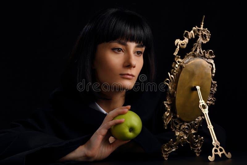 Retrato de uma mulher bonita que olha em um espelho velho imagem de stock