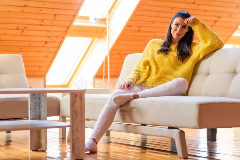 Retrato de uma mulher bonita que relaxa no sofá imagem de stock