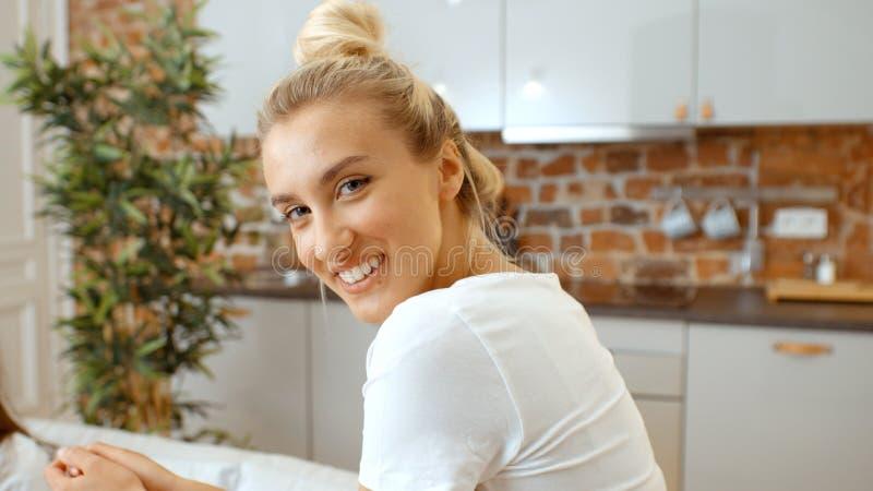 Retrato de uma mulher bonita que sorri a uma câmera em casa fotografia de stock