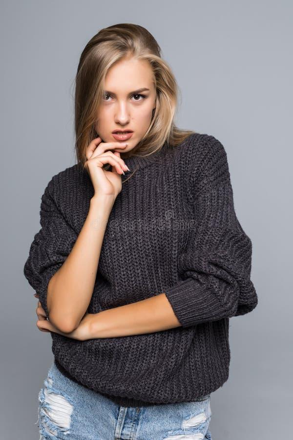 Retrato de uma mulher bonita que veste uma camiseta morna da malha em um fundo cinzento isolado fotografia de stock royalty free