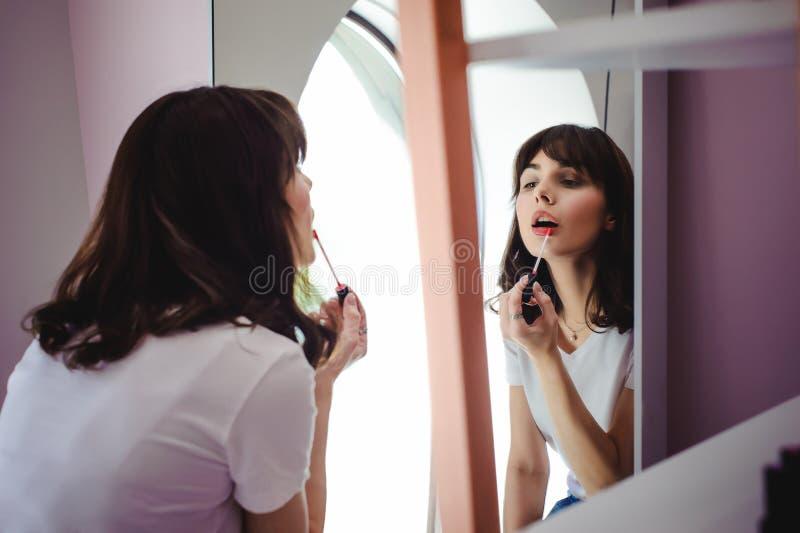Retrato de uma mulher bonita, tinturas seu rosa do batom dos bordos, olhando no espelho fotos de stock royalty free