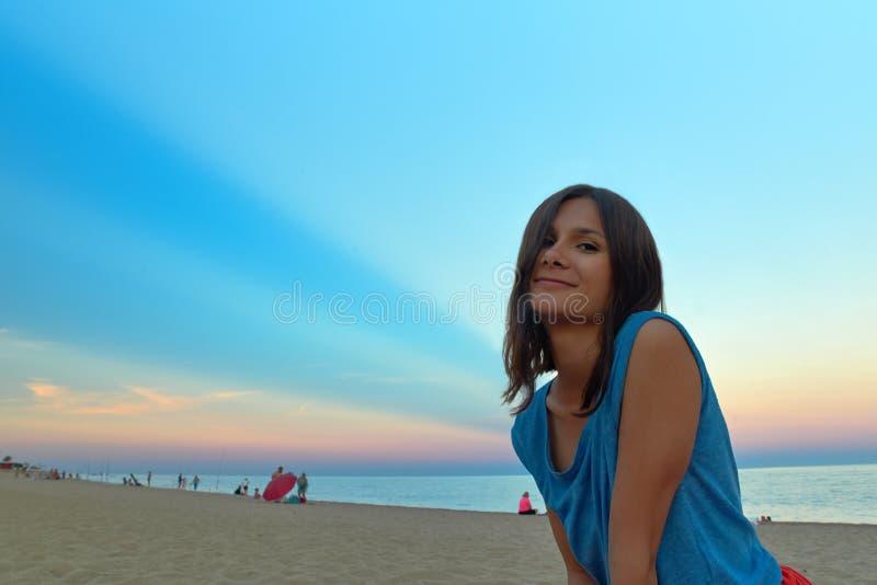 Retrato de uma mulher de cabelos compridos nova no por do sol na praia Co imagens de stock