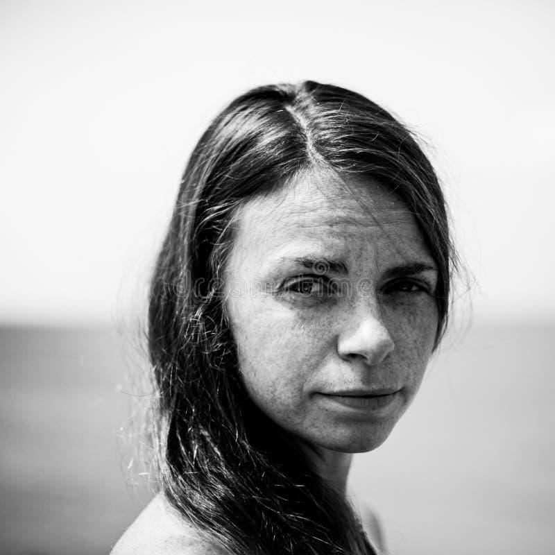 Retrato de uma mulher cansado forte das sardas, foto preto e branco imagem de stock royalty free