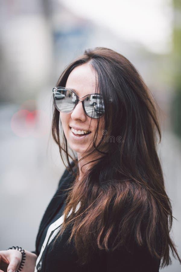 Retrato de uma mulher caucasiano bonita nova no fundo da rua Menina modelo com cabelo e os óculos de sol longos foto de stock