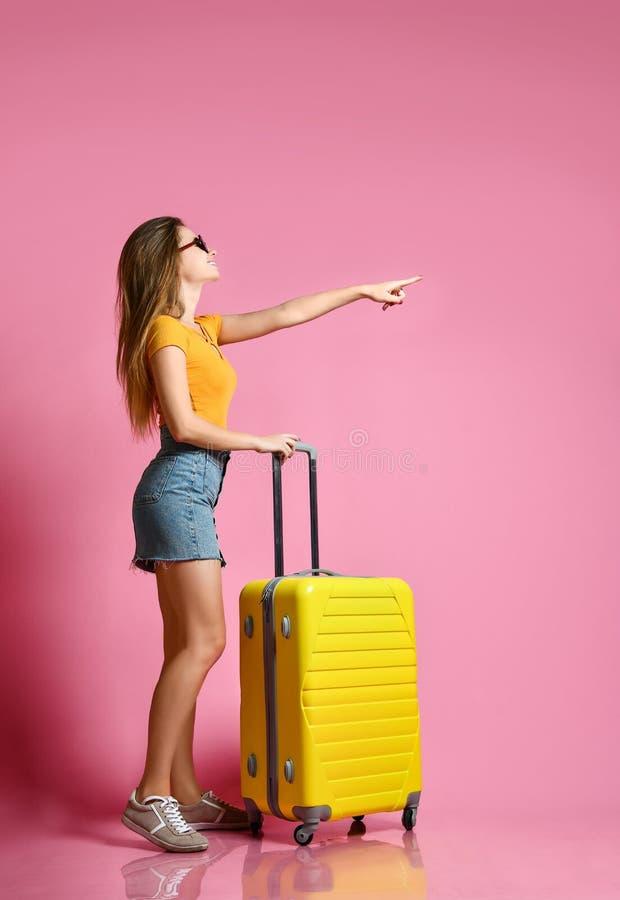 Retrato de uma mulher caucasiano nova alegre vestida na roupa do verão, com uma mala de viagem e apontar um dedo afastado fotos de stock royalty free
