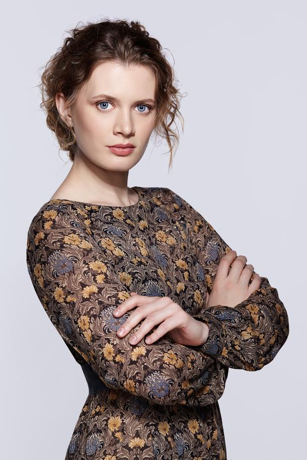 Retrato de uma mulher caucasiano nova no vestido retro do vintage e no cabelo ondulado em um fundo cinzento imagem de stock royalty free