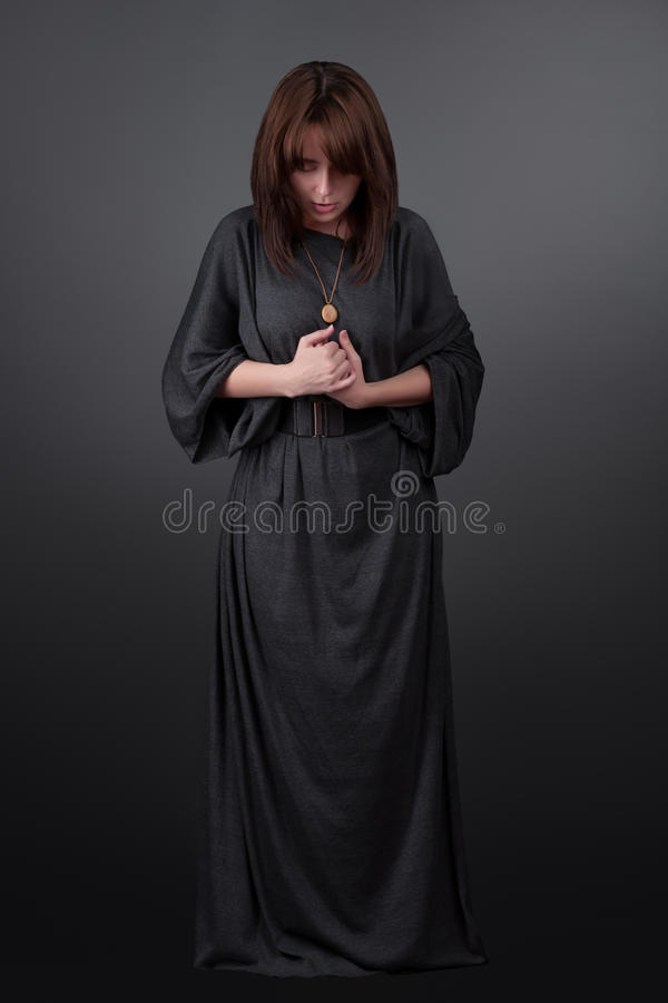 Retrato de uma mulher caucasiano nova que praying A menina da oração vestiu-se nos Vestments de uma freira no fundo cinzento do e fotos de stock
