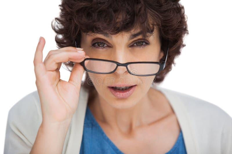 Retrato de uma mulher chocada que olha sobre seus vidros imagem de stock