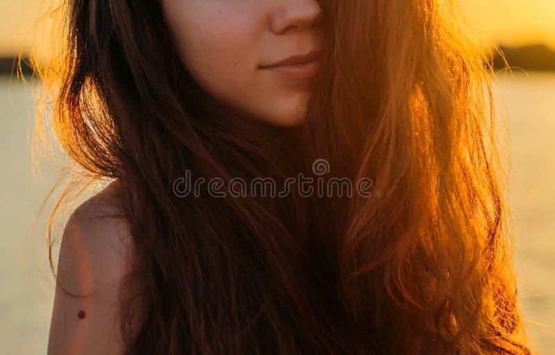 Retrato de uma mulher com cabelo longo no por do sol fotos de stock royalty free