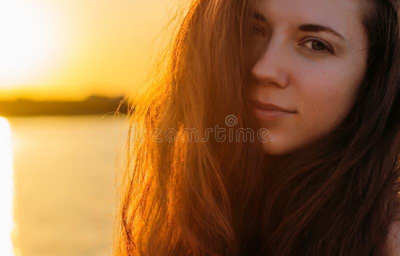Retrato de uma mulher com cabelo longo no por do sol fotografia de stock royalty free
