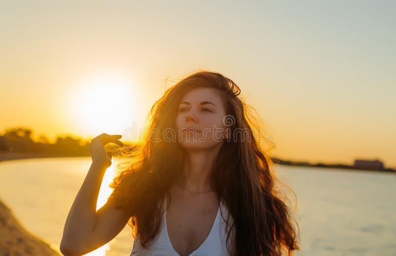 Retrato de uma mulher com cabelo longo no por do sol foto de stock royalty free