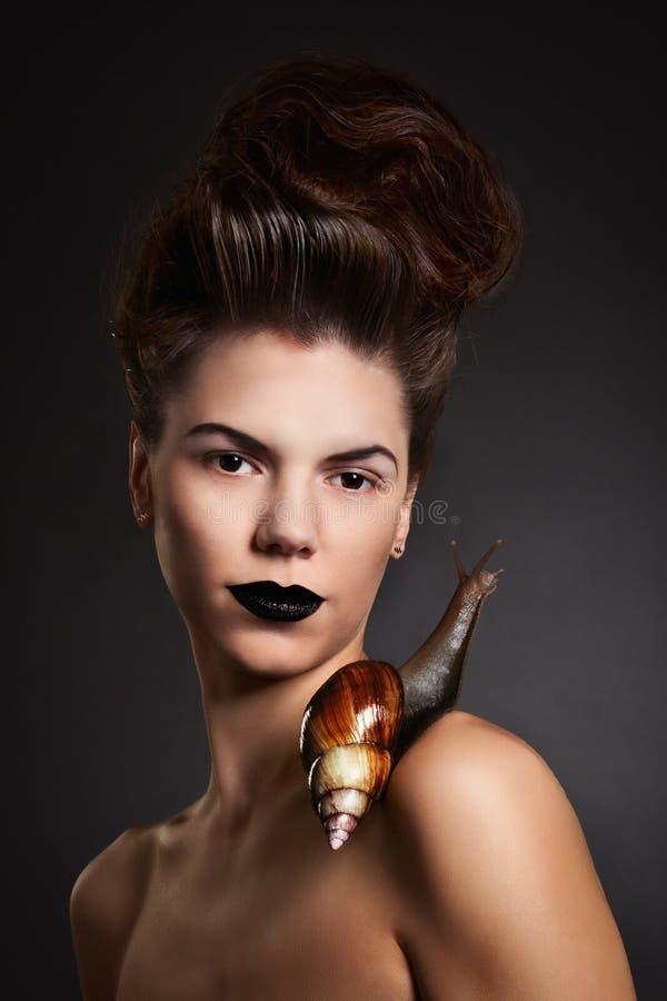 Retrato de uma mulher com o caracol com olhos roxos e bordos. Moda fotos de stock