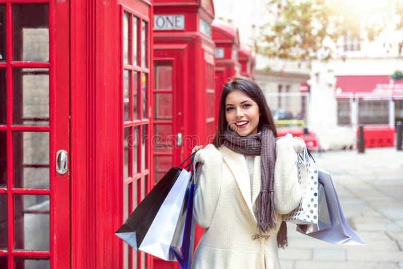Retrato de uma mulher com os sacos de compras em sua mão na frente das cabines de telefone vermelhas em Londres, Reino Unido imagens de stock royalty free