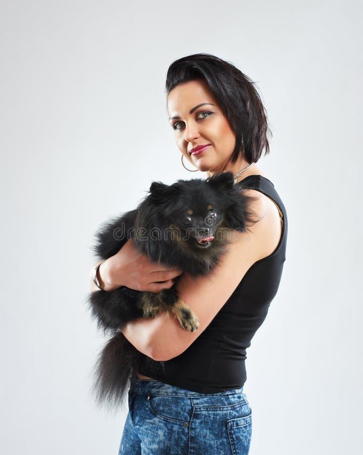 Retrato de uma mulher com um cão preto pequeno imagens de stock royalty free